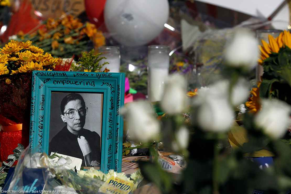 Flowers and a poster with an image of late Associate Justice Ruth Bader Ginsburg are placed outside the Supreme Court in Washington, DC