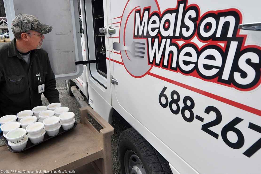 A Meals on Wheels driver loading food into a truck