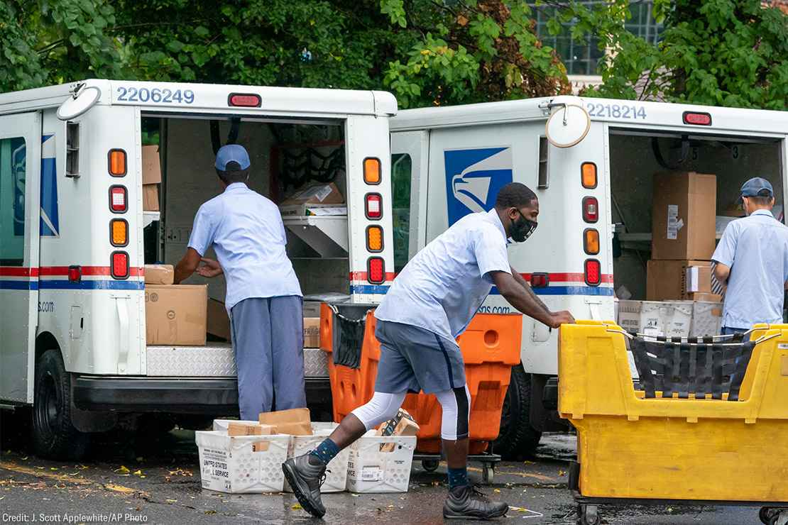 Letter carriers load mail trucks for deliveries at a U.S. Postal Service facility.