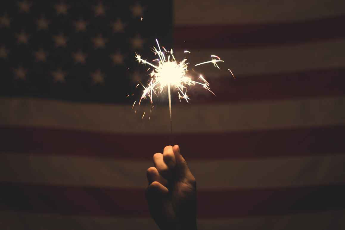 American Flag behind hand holding sparker